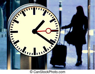 Station clock and a passenger waiting with suitcase.