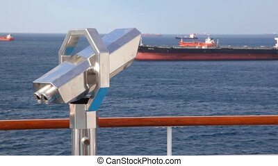 stationary binocular on deck of moving cruise ship in sea...