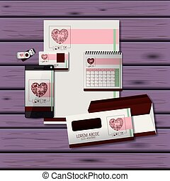 stationary templates of heart design of business stationery over purple wooden background