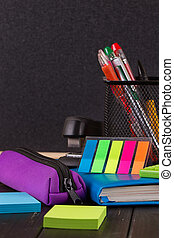 Stationery: pens, pen holder, diary on a black background