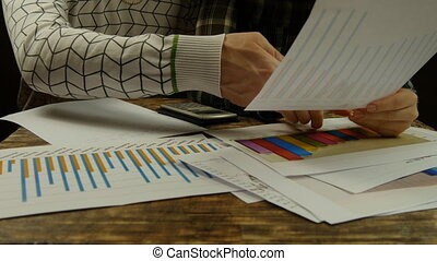 Statistics being pointed at on a desk. Hands of businessman and businesswoman. Close up