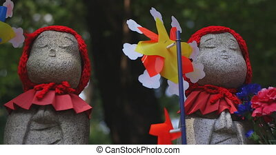 Statue guardian wearing red hat in Tokyo daytime handheld. Minato district Tokyo Japan - 07.25.2019 : It is an old statue at the traditional shrine.