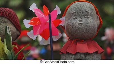 Statue guardian wearing red hat daytime closeup. Minato district Tokyo Japan - 07.25.2019 : It is an old statue at the traditional shrine.