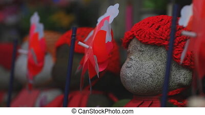 Statue guardian wearing red hat daytime copyspace. Minato district Tokyo Japan - 07.25.2019 : It is an old statue at the traditional shrine.
