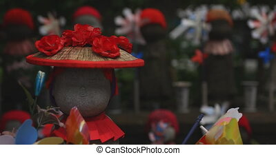 Statue guardian wearing red hat daytime focusing. Minato district Tokyo Japan - 07.25.2019 : It is an old statue at the traditional shrine.