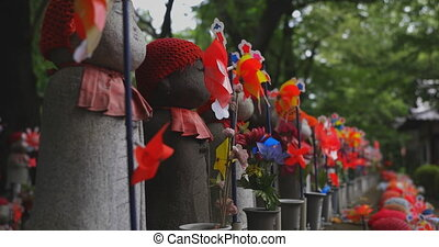 Statue guardian wearing red hat daytime. Minato district Tokyo Japan - 07.25.2019 : It is an old statue at the traditional shrine.