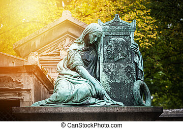 Statue in a cemetery at sunset