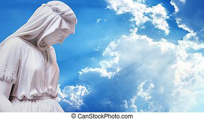 Statue mother of Jesus Christ against blue sky