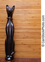 statue of a cat on a background of bamboo mat