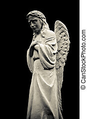 Statue of a crying angel, isolated on black background. Black and white