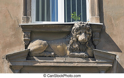 statue of a lying lion under the house window. Lviv