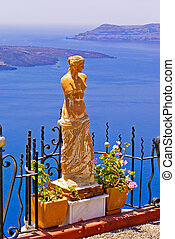 Statue of Aphrodite in Santorini, Greece, Therasia in the backgr