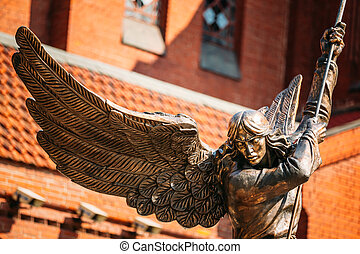 Statue Of Archangel Michael With Outstretched Wings, Thrusting Spear Into Dragon near Red Catholic Church Of St. Simon And St. Helena On Independence Square In Minsk, Belarus