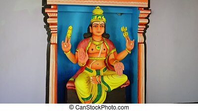 Sculpted and painted image of a god with four hands, wearing ornate robes and a gold crown, in a Hindu temple.