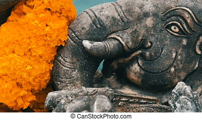 Statue of elephant in flowers close up view. Elephant symbol...