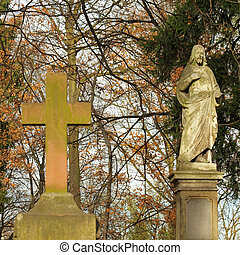 statue  of Jesus on monumental Rakowicki cemetery  in Krakow in autumnal colors