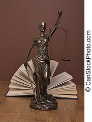 statue of justice, judge's hammer behind books on a braun background