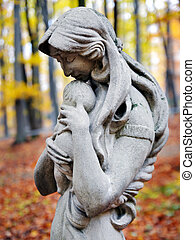 Statue of Madonna and child in autumn forest at cemetery