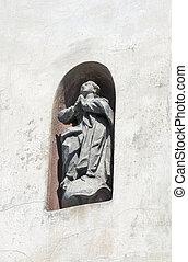 statue of praying man in a wall niche. Lviv.