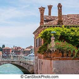 Statue of Saint Mary found on a small street corner of Venice, Italy. Green vegetation.