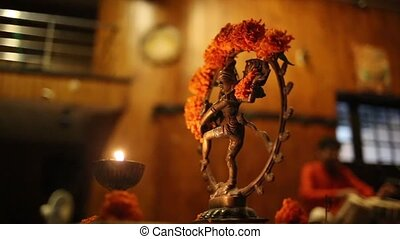 Statue of Shiva, incense and candles in the India