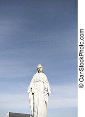 virgin mary against a blue sky