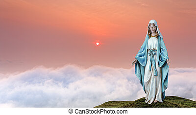 Statue of the Virgin Mary over heavenly sky concept of...