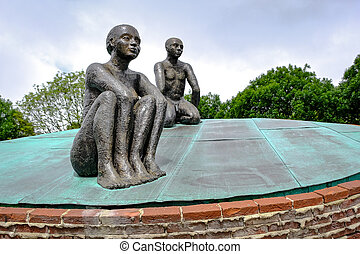 Statue of two people sitting in the park