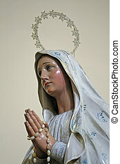 statue of Virgin Mary with hands clasped in prayer