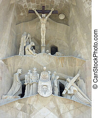 Statues and Jesus Christ on the cross at the entrance of the Sagrada familia church in Barcelona, Spain