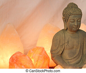 statuette of Buddha in prayer with salt lamps lit during the...