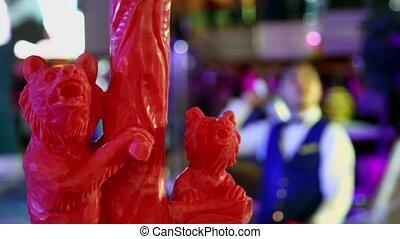 Statuette of two bears, barmen juggles by bottles not in...