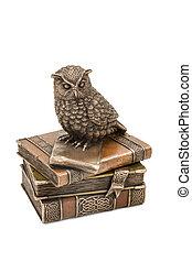 Statuette owl sitting on books