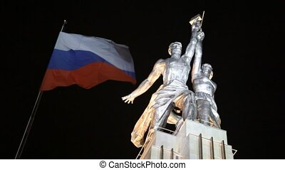 Stature of Worker and Collective farm and russian flag at...