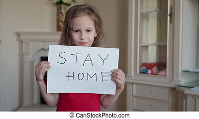 Stay at home concept. Small girl in red T-shirt holding sign...