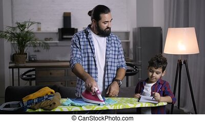 Stay-at-home dad assisting son with schoolwork