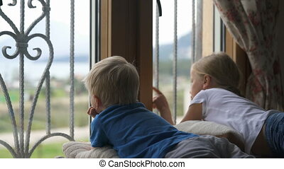 Stay at home quarantine coronavirus pandemic prevention, brother and sister looking out the window unable to go out for a walk
