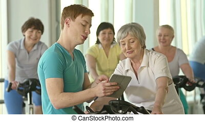 Stay Fit at Any Age - Focus on instructor with tablet and...