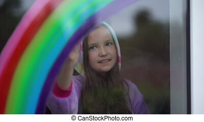Stay home, flash mob chase the rainbow. girl in pajamas draws the rainbow on the window at home.
