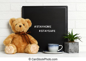 Letterboard with teddy bear, cup of tea and houseplant