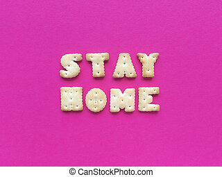 Stay home. Quarantine quote from crackers on pink background. Simple flat lay with pastel texture. Stock photo.