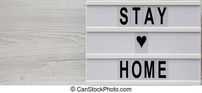 'Stay home' words on a lightbox on a white wooden background, top view. Overhead, from above, flat lay. Copy space.