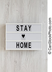 'Stay home' words on a lightbox on a white wooden background, top view. Overhead, from above, flat lay.