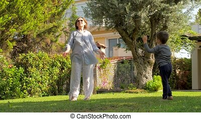 Grandmother with grandson doing morning exercises on backyard. Sport at home during CORONAVIRUS COVID-19 quarantine. Stay fit during quarantine, vacation. Healthy lifestyle background. Raising