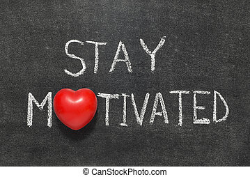 stay motivated phrase handwritten on blackboard with heart...