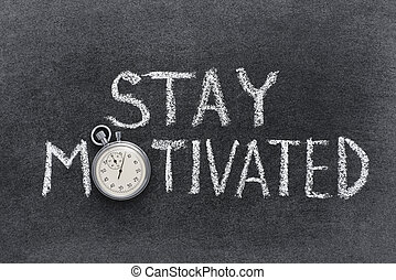 stay motivated phrase handwritten on chalkboard with vintage precise stopwatch used instead of O