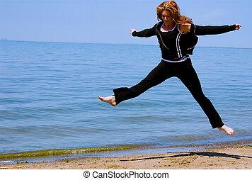A woman leaps high on the beach