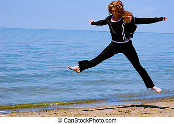 Staying Fit - Jumping - A woman leaps high on the beach