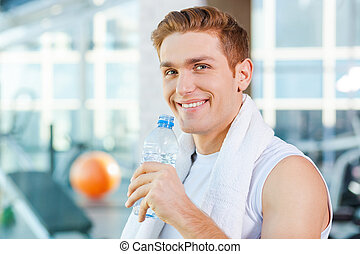 Staying hydrated. Handsome young man carrying towel on shoulders and drinking water while standing in gym