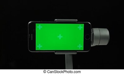 Glare on steadicam with a green screen on mobile phone for shooting smooth video. Professional equipment for the filmmaker. Anti vibration, anti shake. Close-up motion on black background.